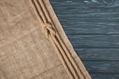 vue de dessus de corde nautique marron nouée sur un sac sur fond en bois