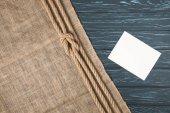 vue de dessus de corde nautique marron nouée sur un sac et l'absence de papier sur une surface en bois