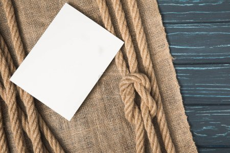 closeup shot of blank white paper on sackcloth and brown nautical knotted ropes on wooden tabletop