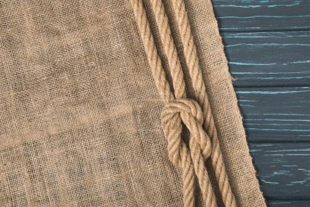 top view of brown nautical rope with knot on sackcloth