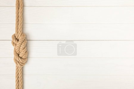 Photo for Top view of brown nautical rope with knot on white wooden surface - Royalty Free Image