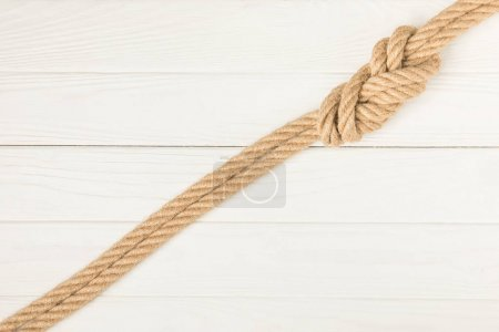 top view of brown nautical rope with knot on white wooden surface