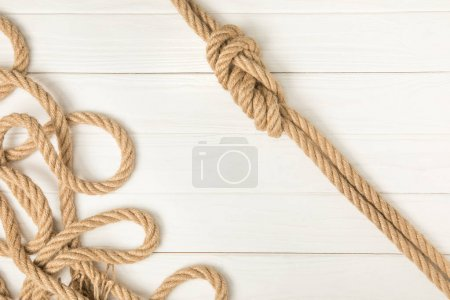 top view of brown nautical knotted ropes on white wooden planks
