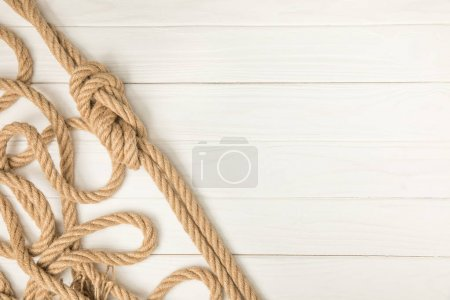 top view of brown nautical knotted rope on white wooden planks