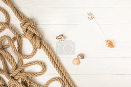 top view of brown nautical knotted rope and empty paper with seashells on white wooden surface