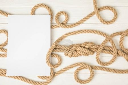 top view of empty paper on brown nautical knotted ropes on white wooden surface