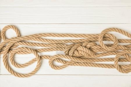 Photo for Top view of brown nautical knotted ropes on white wooden surface - Royalty Free Image