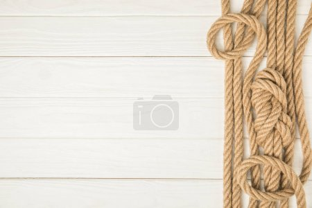 top view of brown nautical knotted ropes on white wooden background