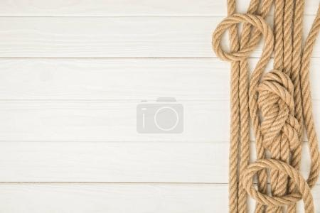 Photo for Top view of brown nautical knotted ropes on white wooden background - Royalty Free Image