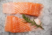 top view of sliced red fish with rosemary branch on crushed ice