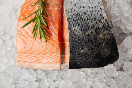 top view of sliced red fish fillet with rosemary on crushed ice