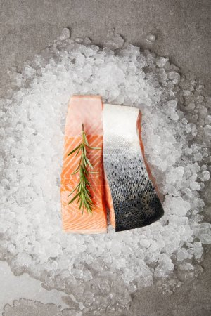 top view of sliced salmon fillet with rosemary on crushed ice and on concrete surface