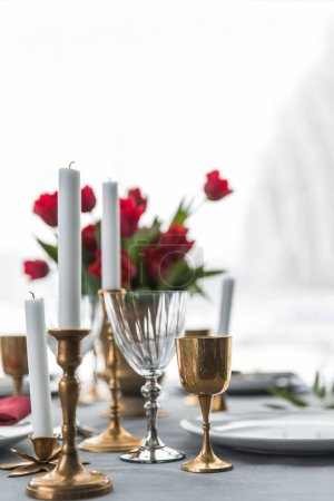 selective focus of candles in vintage candle holders, bouquet of red tulips and arranged empty plates on tabletop