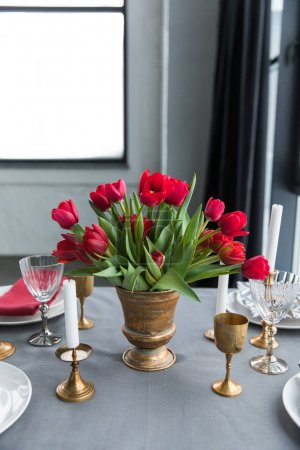 close up view of bouquet of red tulips on tabletop with arranged vintage cutlery and candles
