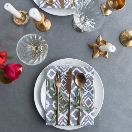 flat lay with beautiful rustic table arrangement with old fashioned tarnished cutlery and wine glasses