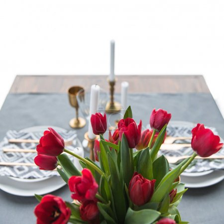 selective focus of bouquet of red tulips and rustic table setting behind