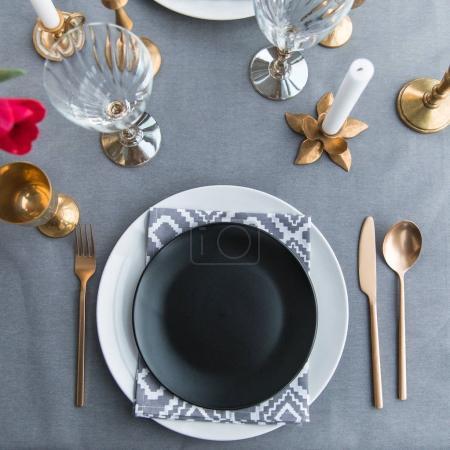 Photo pour Lay plat avec une plaque vide noire, vieux façonné ternie couverts et verres à vin vides sur la table - image libre de droit