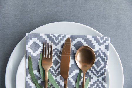 flat lay with rustic table setting with vintage tarnished silverware, napkin, green plant and plate