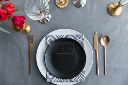 top view of black empty plate, napkin and old fashioned tarnished cutlery on tabletop