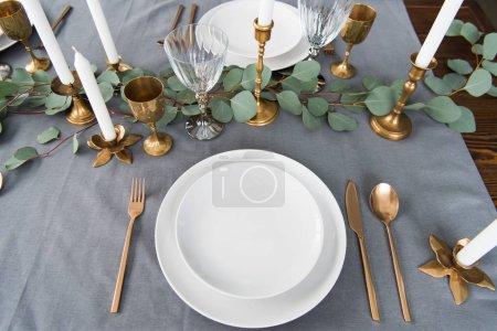 Photo pour Gros plan vue d'arrangement de table rustique à l'eucalyptus, couverts vintage, bougies dans des bougeoirs et des assiettes vides - image libre de droit