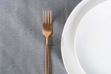 top view of arranged tarnished old fashioned fork and empty plates on tabletop
