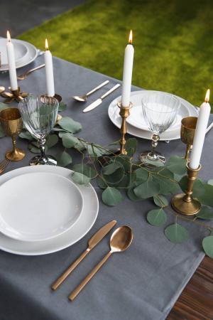 Photo pour Bouchent la vue du paramètre table rustique à l'eucalyptus, vintage couverts ternis, bougies dans des bougeoirs et des assiettes vides - image libre de droit