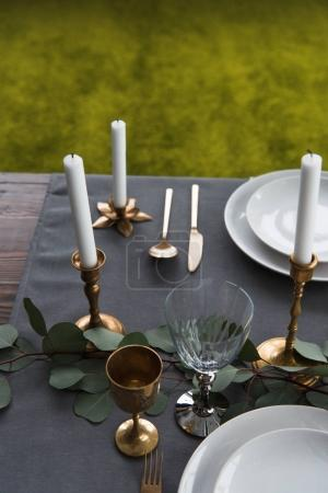 close up view of rustic table arrangement with winecups, eucalyptus, vintage cutlery, candles in candle holders and empty plates