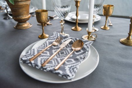 close up view of rustic table setting with old fashioned cutlery and napkin on plates, candles and empty wine glasses on surface