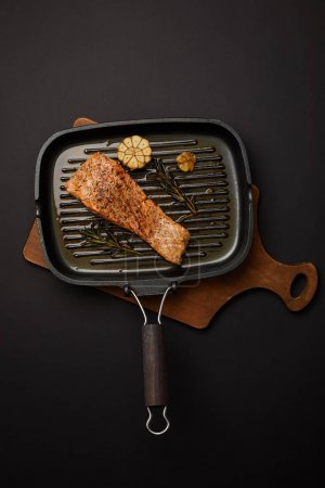 top view of arranged grilled salmon steak with rosemary on wooden cutting board on black tabletop