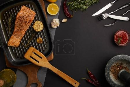 top view of arranged grilled salmon steak on wooden cutting board, ingredients, sauce and cutlery on black tabletop