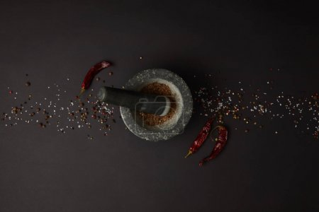 Photo for Flat lay with mortar, pestle, spices and chili peppers on black tabletop - Royalty Free Image