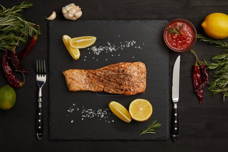 top view of grilled salmon steak with pieces of lemon, arranged ingredients around and cutlery on black surface