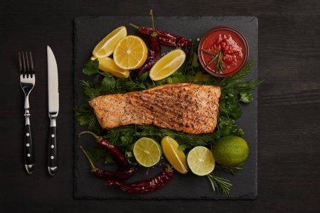 Photo pour Vue de dessus de Darne de saumon grillé, des morceaux de citron vert et citron, la sauce et couverts sur une surface noire - image libre de droit