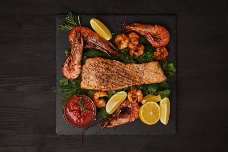 top view of grilled salmon steak, shrimps, pieces of lemon and sauce on black surface