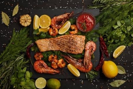 top view of grilled salmon steak, shrimps, pieces of lemon, sauce and spices on black surface