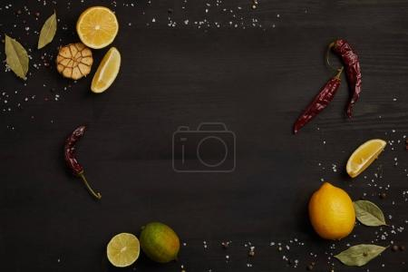 flat lay with lemon and lime pieces, spices, chili peppers and bay leaves on black tabletop