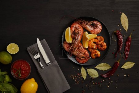 flat lay with grilled shrimps with lemon pieces on plate and arranged sauce, spices, ingredients and cutlery around on black surface