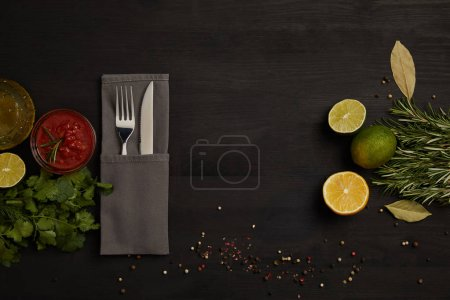 flat lay with cutlery, sauce, rosemary, spices and citrus fruits pieces on black tabletop