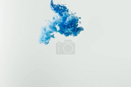 Photo for Close up shot of bright blue paint splash in water isolated on gray - Royalty Free Image