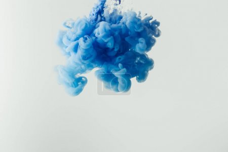 close up shot of bright blue paint splash in water isolated on gray
