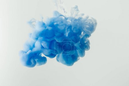 Close up shot of bright blue ink splash in water isolated on gray