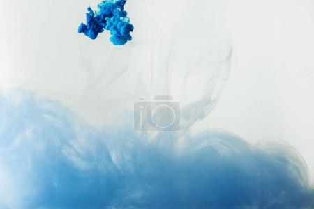 Photo for Close up view of mixing of blue and light blue paints splashes  in water isolated on gray - Royalty Free Image