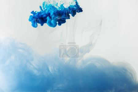 bouchent la vue du mélange de bleu et bleu clair peint des éclaboussures dans l'eau isolé sur gris