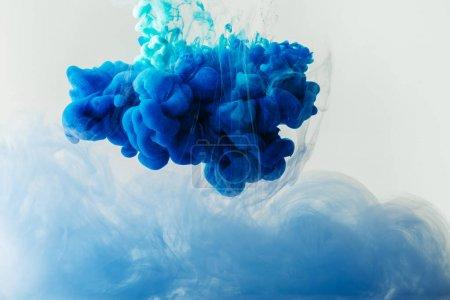 Nahaufnahme der Mischung aus blauen und türkisfarbenen Farbspritzern im Wasser isoliert auf grau