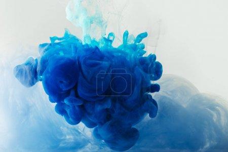 Photo pour Bouchent la vue de mélange d'éclaboussures de peinture bleue et turquoise en eau isolé sur gris - image libre de droit