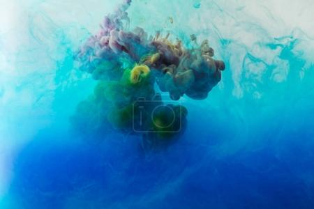 full frame image of mixing of blue, turquoise and yellow paints splashes  in water
