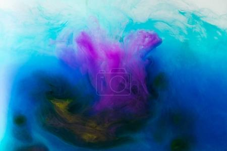 full frame image of mixing of blue, turquoise, yellow and purple paints splashes  in water