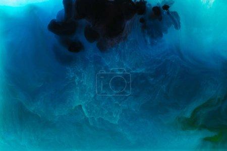 Photo pour Image plein cadre de mélange de bleu, noir, turquoise et vert peint des projections dans l'eau - image libre de droit