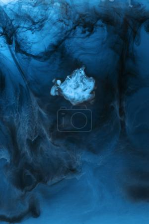 full frame image of mixing of light blue and black paints splashes in water
