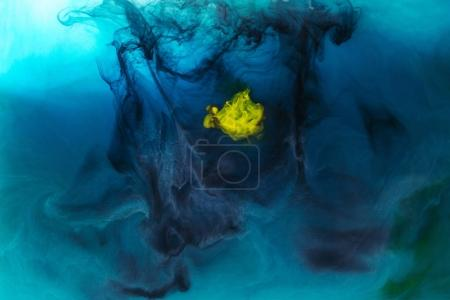Photo for Full frame image of mixing of blue, black, yellow and green paints splashes in water - Royalty Free Image